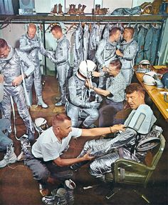 The Seven Astronauts of the Mercury Program try on their distinctive silver space suits.