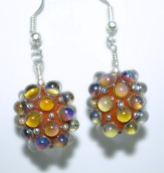 Handcrafted glass bead earrings using my, SRA Artisan Lampwork beads consisting of orange brovn base, blue, and silver . The beads are made with a bumpy detail in dyp blue and silver over an orange b