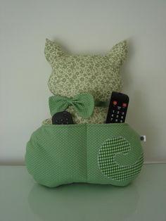 Almofada porta controle remoto no formato de gata feita em tecido 100% algodão e com enchimento super macio anti alérgico.    **Medida: 38cm de altura X 34cm de largura**  **Controles NÃO acompanham a almofada** R$ 47,00