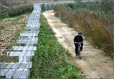 A Chinese farmer rides a bicycle Monday beside the fence along a dam, which borders China and North Korea, in the Chinese city of Dandong.