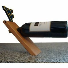 NCAA Floating Stand Tabletop Wine Rack NCAA Team: West Virginia by Fan Creations. $16.99. C0540-West Virginia NCAA Team: West Virginia Features: -Floating bottle stand.-Material: Wood.-The athletic logo is carved out and mounted on top of the stand. Dimensions: -Overall dimensions: 10'' H x 12'' W x 3'' D.
