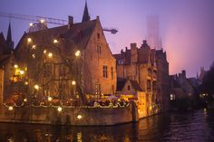 Beautiful corner lit up at sunset in Brugge (Bruges), Belgium in winter for Christmas. Foggy belfry and Christmas lights over the canal.