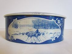 Vintage oval delft blue Droste Haarlem Holland chocolate candy tin measures 7 x 4 x 2.75. Tight fitting, weighted lid is rounded on top. Design is of sailing ships on the lid and images on the sides are a field with windmills, animals being herded in a field and a cow in the pasture. Has