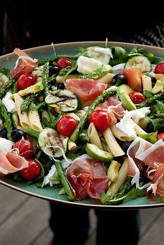 Lentefris zomerslaatje: rucola, groene asperges, mozzarella, avocado, gedroogde ham (type parma), zwarte olijven, kerstomaatjes, courgette