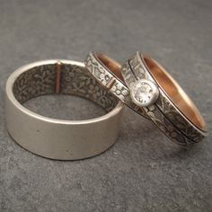 A new Opposites Attract set, this one with a forget me not pattern. The customer is in Hawaii and wanted something reminiscent of the floral designs that are typical there (think Hawaiian shirt). The woman's wedding band is 3mm wide with a rose gold tab. The matching engagement ring is 5mm wide with the pattern split by a line and a 4mm round moissanite set in a conical silver bezel setting. The man's ring is 10mm wide.