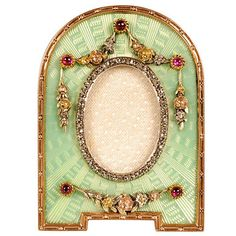 A Faberge gem-set, gold, and guilloche enamel frame, workmaster Victor Aarne, St. Petersburg, circa 1899-1908. The domed frame on bracket feet enameled in pale translucent green enamel over a radiating engine-turned ground, the mine-cut diamond oval aperture surrounded by applied three-color gold chased floral swags and cascades accented by cabochon rubies.