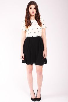 Sugarhill Boutique Heart Print Dress. Heart print top. Black skirt. Fit and flare shape. Round neckline.