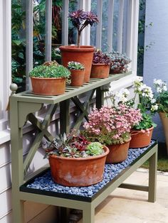 A tiered garden stand is a great way to display flowering plants on a backyard patio. The first level is lined with gravel to provide good drainage for plants.