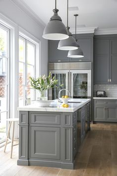 Three large pendant lights hang over a gray and marble kitchen island.