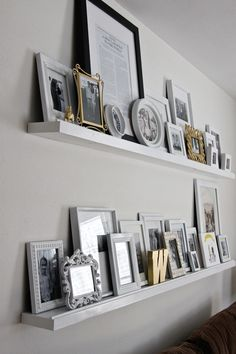 floating shelves with staggered photos. love this for a living room.