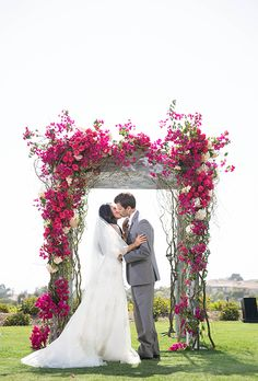 Brides.com: 30 Amazing Ceremony Structures. A romantic floral arbor covered in bright bougainvillea, fushia roses, and blush hydrangeas, created by Sunny Ravanbach of White Lilac Inc.