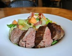 Grilled Filet Tail Kiss Melon Salad. It comes with grilled USDA choice Harris Ranch filet tail with Summer Kiss melons tossed with prosciutto, nectarines, yellow peaches, fresh basil, romaine, fresh mozzarella cheese, red onion, avocado, cucumber white balsamic vinaigrette.
