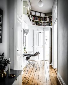 Hallway incorporates book cases and uses natural tone of the pine flooring to offset the white decor in this apartment in Stockholm Sweden. [1080  1349]