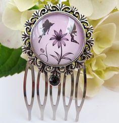 Dieser kleine Haarkamm besteht aus silberfarbenem Metall und einer filigranen Fassung. Der handgearbeitete Glas-Cabochon zeigt ein wunderschönes Elfen