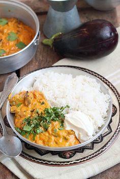 Délices d'Orient: Curry d'aubergine 2 aubergines 1 gros oignon  500 gr de tomates épépinées et coupées en dés Un tronçon de 5 cm de gingembre frais  1 c.à.c de gingembre 1 c.à.c de curcuma 3 gousses d'ail 1 c.à.c de coriandre en grain 1 c.à.c de piment pili pili 1 c.à.c de poivre grossièrement concassé  1 c.à. c de graines de cardamome Sel 4 c.à.s d'huile d'olive 300 ml de lait de coco Coriandre fraîche et yaourt nature pour servir