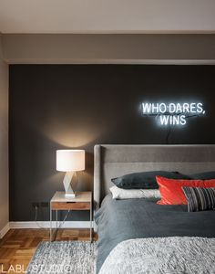 """The ultimate alpha apartment bedroom painted in Benjamin Moore Cumulus Cloud and Kendall Charcoal with """"Who Dares, Wins"""" white neon sign. A Gus Carmichael bed is dressed with masculine bed linens from West Elm and a Paul Smith for Maharam pillow in epingle stripe. A steel and wood Audrey nightstand from CB2 flanks each side of the bed. Interior Design by LABLstudio."""