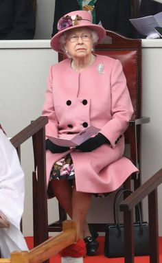 Queen Elizabeth II wearing a powder pink ensemble, attends the decommissioning ceremony for HMS Ocean on March 27, 2018 in Plymouth, England.