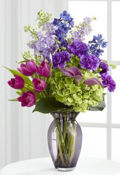 A vase arrangement of tulips, carnations, larkspur, delphinium, miniature calla lilies and hydrangea blooms.
