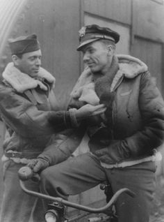 """UNITED STATES EIGHTH AIR FORCE IN BRITAIN, 1942-1945. Captain John Bostick (left) of the 94th Bomb Group greets his colleague Lieutenant R.A Senior, and his pet cat """"Smokey Joe"""" who is tucked into Senior's jacket."""