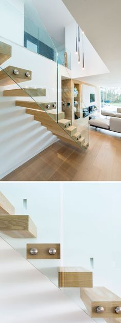 This modern wood and glass staircase leads to the upper floor of this house.