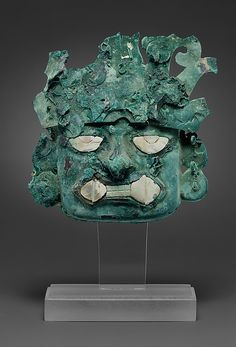 Silvered copper ornamental mask   The inlays are made from sea shells. 9.5 cm high and 10 cm wide (3 3/4 x 3 1/5 inch.)   Found in Peru, from the Moche culture (Lome Negra), around 400 AD  Source: Metropolitan Museum