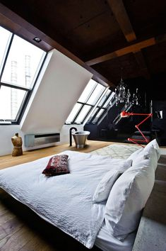 Industrial loft space with low bed and red, extendable light