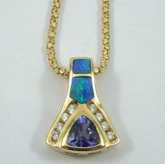Trillian Cut Tanzanite Necklace with Opal & Diamond Accents. Set in 14K Yellow Gold. With 14K Yellow Gold Chain.  $675