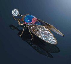 AN UNUSUAL MULTI-GEM BROOCH, BY WALLACE CHAN DESIGNED AS A CICADA HOLDING A CUSHION-SHAPED DIAMOND, THE HEAD AND BODY SET WITH BLACK OPAL AND LAPIS LAZULI WITH CARVED AMETHYSTS ATOP, TO THE CABOCHON RUBY EYES AND PINK SAPPHIRE DETAIL, EXTENDING TO THE WHITE TO GREY CRYSTAL AND MOTHER-OF-PEARL WINGS WITH TITANIUM VEINS, MOUNTED IN TITANIUM AND 18K GOLD, 8.0 CM LONG SIGNED WALLACE CHAN