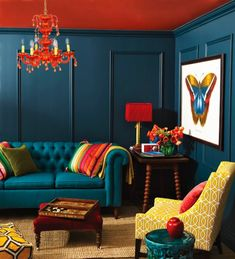 Paint colors. LOVE! Also a huge fan of the tray on the end table as well as the large, bright print that pops from the wall. Gold slip covers on the couches? Floral pillows in contrasting reds and blues?