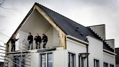 Builders on the first floor of a house after its wall was blown away by windstorms