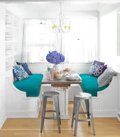 bright dining space with white bench, turquoise cuscions and metal stoods #diningnook
