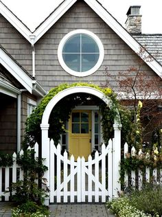grey house, white trim, yellow door beautiful gate framing the door too