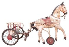 Toy Pedal Horse, C. 1930  |   Antique toy pedal riding cart harnessed to a white cast metal horse. Original rubber tires and leather reins. Chain guard missing. Circa 1930. Thought to be French. No metal damage. Displays very well.  55'' L x 19'' W x 35'' H - $1,595.00.