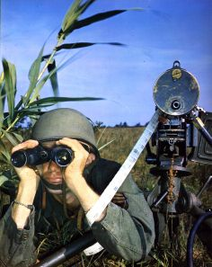 T/Sergeant John Carter, uses a pair of 6x30 Westinghouse binoculars to observe enemy activities for range on his 30 caliber water cooled machine gun, May 1945. (Photo by PhotoQuest/Getty Images)