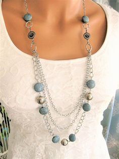 Long Blue-Gray Multi Strand Beaded Necklace handmade by Ralston Originals. This blue-grey beaded necklace is made with 3 multi strands of long silver chain, large silver rings, and blue-gray, and silver acrylic beads. The acrylic beads make this necklace lightweight and comfortable.