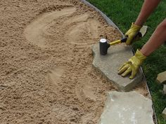 Modern Flagstone Walkway Ideas | Step 4: Make sure each stone is set firmly into the sand by hitting it ...