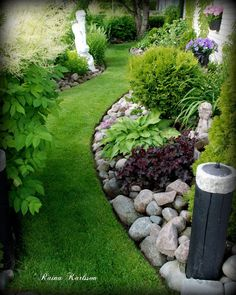 Curved flower bed with rock landscaping and plantings that add color and texture.