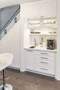 This home added a coffee station and food storage cabinet under the stairs. The space, located just off the kitchen, was opened up to enable it to be dedicated to coffee making. Lights, shelving, and cabinetry were installed, as well as a small sink with tile backsplash.
