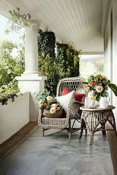 Porch with heavy columns and natural wicker chair and table.