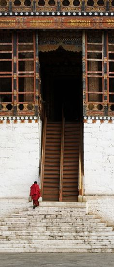 A buddhist Monk in Bhutan hauls fresh water from the nearby river up the long steps of the monastery