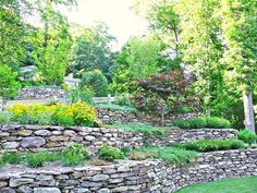 How to Landscape a Sloped Yard Stone walls are a classic way to terrace a sloping hillside. The post How to Landscape a Sloped Yard appeared first on Gartengestaltung ideen. Terraced Backyard, Terraced Landscaping, River Rock Landscaping, Landscaping On A Hill, Large Backyard Landscaping, Landscaping With Rocks, Landscaping Ideas, Backyard Ideas, Inexpensive Landscaping
