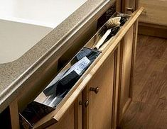 FLIP DOWN UTENSIL TRAY-These are great for pads, sponges, and scrub brushes. Available in plastic and stainless. You have space between your panel at your sink and your sink bowls, so you might as well use it. Utensil trays can be ordered to retrofit in existing cabinets or ordered with new cabinets.