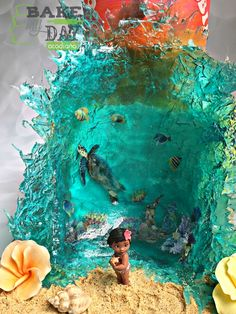 Birthday Cakes - Bake My Day Acadiana. Baby Moana inspired birthday cake with isomalt wave, tropical hibiscus flowers, sunset buttercream cake, sea turtles, tropical fish inside the wave, edible sand, and modeling chocolate seashells