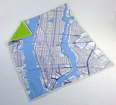 """MANHATTAN BABY QUILT  Cuddle up with the city that never sleeps. Made of natural cotton and a thick 100% cotton batting, the quilt is perfect for snuggling or as a newborn's keepsake gift. Each 42"""" x 36"""" quilt is custom printed and hand-knotted,and available in three colorways."""