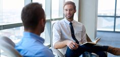 Young businessman sitting comfortably in an open modern office, smiling while having a positive conversation with a coworker Communication Skills Training, Helfer, Effective Communication, Workplace, Conversation, Photo Editing, Positivity, Stock Photos, Learning