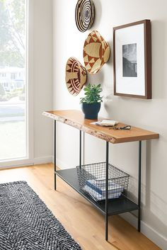 The wood top of our Chilton console table is paired with a natural steel base and shelf for a modern look that allows you to double up on storage and display.