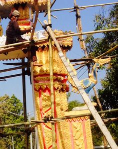 A local painter is restoring the main gate to the Buddhist temple in Nikom Lom Soi, thailand.