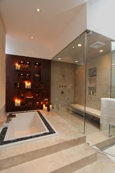 A relaxing spa environment! An over-sized steam shower completes the experience. A richly stained feature wall with softly lit niches and shelves can be refreshed by changing out decorative items seasonally. (project done by Arch-Interiors)