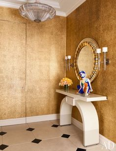 Clad in gold leaf, the elevator foyer is further enlivened by a circa-1940 Venini hanging lamp and a circa-1950 Fontana Arte mirror | archdigest.com