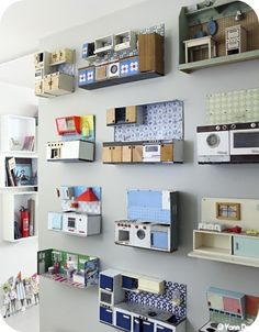 Great way to display a collection of miniature dolls house kitchens.